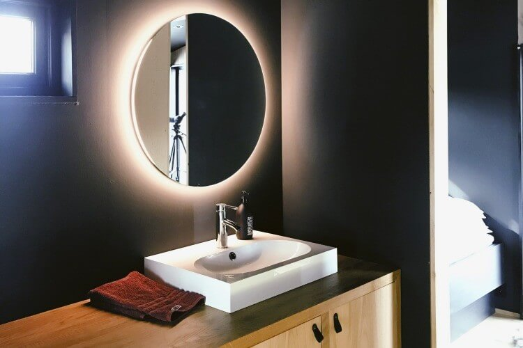 Bathroom with black walls and wooden cabinets