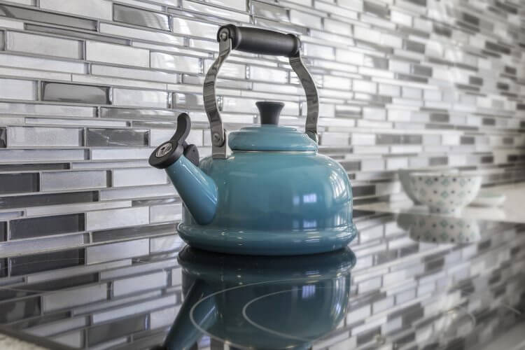 Small thin tiles on kitchen wall behind kettle